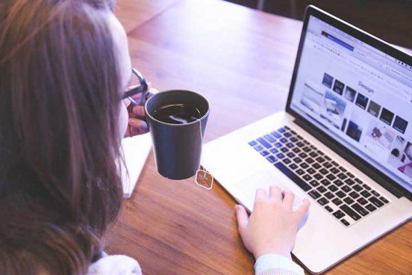 девушка с чаем смотрит в ноутбук