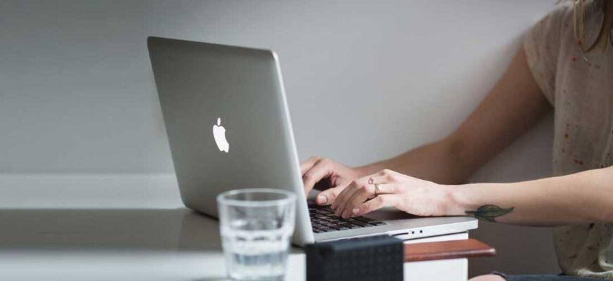 Девушка сидит за макбуком